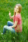 Smiling female sitting outdoors gesturing thumb up