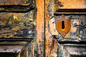 stock photo of peep hole  - Detail of vintage key hole on weathered wooden door