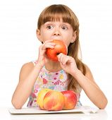 Portrait of a cute cheerful little girl is biting red apple, isolated over white