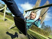 stock photo of swings  - Carefree child on a swing in a park on summer day - JPG