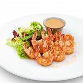 Delicious healthy cooked royal shrimps served with ruccola salad and sauce. Isolated on white.