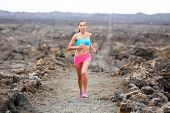 Runner woman triathlete trail running cross country running outdoors on volcano. Female athlete jogg