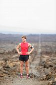Running man - portrait of male runner resting after cross country run on trail. Fit handsome athlete taking break standing in amazing volcano landscape on Big Island, Hawaii, USA.