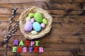 Easter eggs in nest, pussy-willow and sign on color wooden background