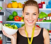 Closeup portrait of cute smiling woman with measure tape and fresh vegetables salad, sportive traine