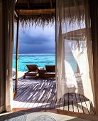 Luxury romantic place for honeymoon, beautiful wooden bungalow on the water, two deckchair on the terrace, vacation on Maldives, summer time concept