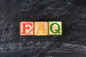 Colorful childrens blocks spelling out FAQ on a chalk board. Horizontal format.