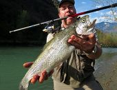 picture of steelhead  - a fisherman holding a fresh caught fish - JPG