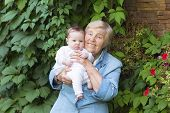 Great-grandmother Holding A Newborn Baby