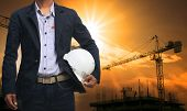 image of structural engineering  - engineer man standing with white safety helmet against beautiful dusky sky with building construction site use for engineering and construction industrial business - JPG