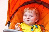 Funny Toddler Boy Smiling Outdoor In Orange Stroller