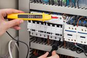 Electrician Examining Fusebox With Voltage Tester