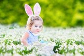 Adorable Toddler Girl Wearing Bunny Ears Playing With Easter Eggs In A White Basket
