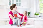 Young Laughing Toddler Girl And Her Beautiful Young Mother Making Fresh Strawberry And Other Fruit