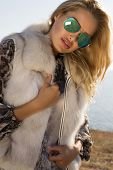 Portrait Of Beautiful Woman With Blond Hair In Fur Coat And glasses