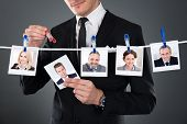 Businessman Selecting Candidate From Clothesline