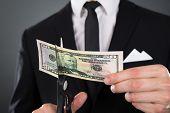 Businessman Cutting Dollar Bill With Scissors