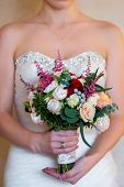 stock photo of wedding feast  - Bride holding a wedding bouquet of pink roses.