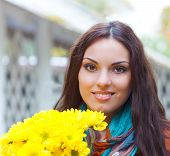 Beautiful Smiling Woman With Flowers In Autumn Park