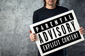 Man Holding Poster With Parental Advisory Label