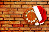 Santa Claus Hat On New Year's Night On The Old Clock Showing Twelve O'clock On The Brick Background