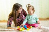 Happy Mother And Kid Play With Toys At Home