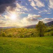 Village On Hillside Meadow In Mountain At Rainbow Sunset