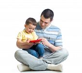 Father And Kid Are Looking To Play And Read Tablet Computer