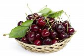 Cherries in a wicker basket with a leaf on a white background