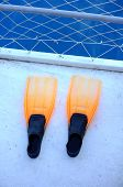 Orange flippers on boat dock