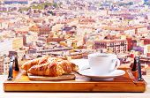 Cup Of Coffee And Croissants Over Cityscape