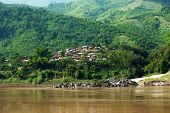 Small Asian Village With Traditional Wooden House In Jungles Along Mekong River. Laos Countryside