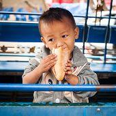 Cute Boy Enjoying Sandwich At Asian City Street. Luang Prabang, Laos