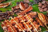 Traditional Asian Food At Market. Delicious Spicy Grilled Pork Meat