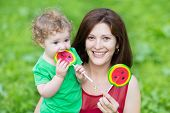 Young Beautiful Mother And Her Adorable Curly Baby Daughter Eating Watermelon Candy In A Park