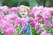 Portrait Of A Beautiful Curly Baby Girl With Blue Eyes In A Field Of Pink Flowers