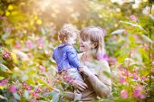 Beautiful Woman Playing With A Happy Baby Girl In A Garden At Sunset