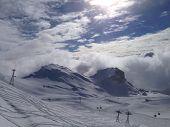 A Mountain Ski Scene Under A Bright Blue Sky With Clouds