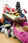 stock photo of untidiness  - Untidy stack of shoes thrown on the ground - JPG
