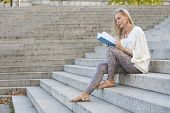 Woman Sitting On Stairs And Reading A Book