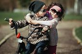 little boy and girl ride bike