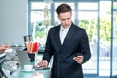 Recruitment. Confident And Successful Businessman Standing In An Office And Holding A Mobile Phone I