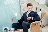 Coffee Break. Confident And Successful Businessman Sitting In An Office And Is Working At The Comput