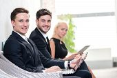 Job Candidates. Three People In Formalwear Waiting In Line While Sitting At The Chairs And Holding L