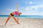 stock photo of legs apart  - Smiling young woman stretching body with one arm up and legs apart in yoga position on sandy beach with beautiful ocean background - JPG