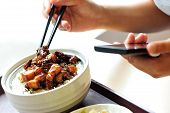 woman eat chinese food use her cell phone