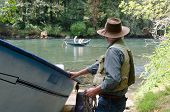 picture of mckenzie  - A fisherman prepares to put his drift boat into the Mckenzie River near Eugene Oregon as he watches another boat already on the water - JPG