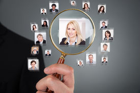 foto of candid  - Cropped image of businessman searching candidate with magnifying glass over gray background - JPG