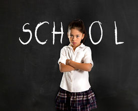 stock photo of hate  - latin moody little girl in uniform standing upset in front of blackboard with school written with chalk in I hate studying and learning is boring concept - JPG