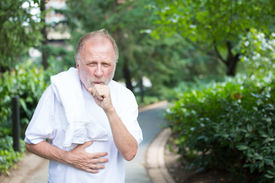 picture of pneumonia  - Closeup portrait old gentleman in white shirt with towel coughing and holding stomach isolated green trees and shrubs outside outdoors background - JPG